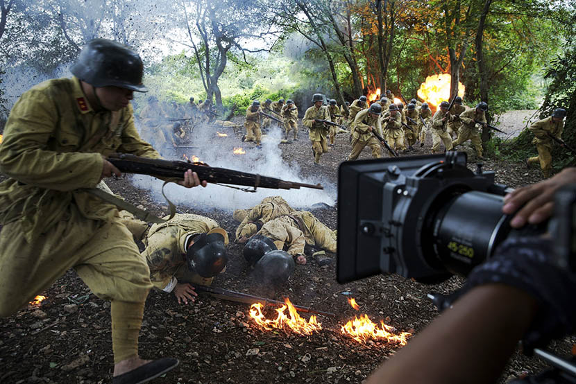 The camera rolls as actors dressed as wartime Chinese soldiers act out an attack by enemy artillery, July 24, 2015. Filming of the television series takes place near Hengdian World Studios, Zhejiang province.  Damir Sagolj/Reuters/VCG
