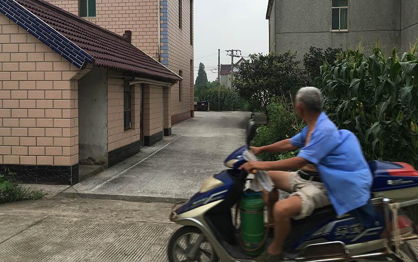 A man riding a motorcycle through Zhanhong Village, Chongming County, Shanghai, July 14, 2016. Ni Dandan/Sixth Tone