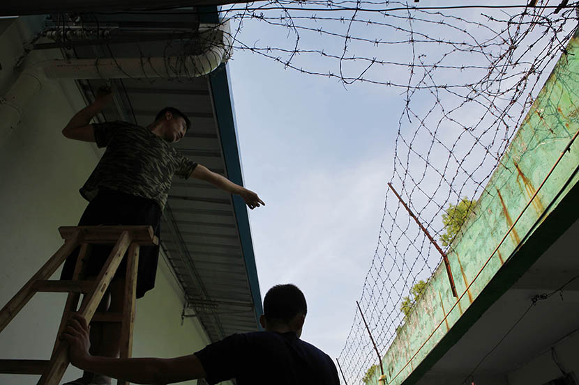 Two men install barbed wire fencing to prevent students from escaping a military-style internet addiction treatment center in Huizhou, Guangdong province, Aug. 18, 2016. Chen Weibin/ Nanfang Metropolis Daily/VCG