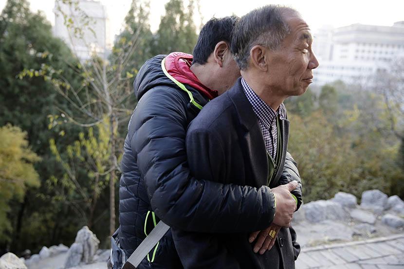 Peng Huijie is hugged by man at Dongdan Park in Beijing, Nov. 24, 2014. Dong Dalu/Sixth Tone