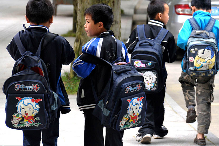 Students carry heavy backpacks on their way home after school in Jinggangshan, Jiangxi province, May 26, 2010. Li Wenming/VCG