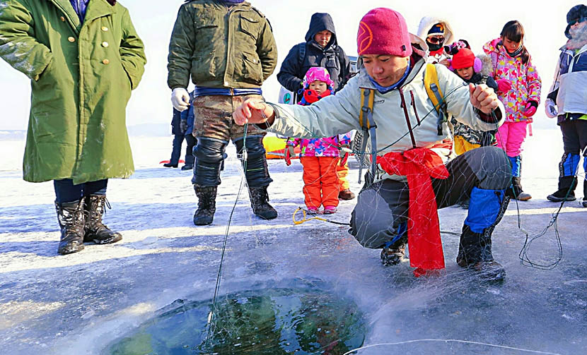 He Junheng teaches his students how to ice fish during Jiabeicun's winter tour in Mudanjiang, Heilongjiang province, Jan. 17, 2016. Courtesy of Jiabeicun