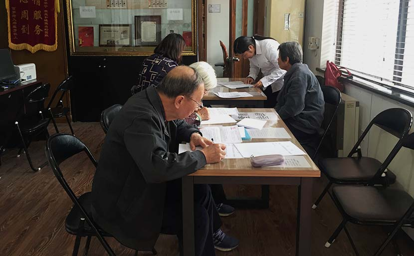 Several elderly people write wills by hand at the China Will Registration Center in Beijing, Oct. 18, 2016. Wang Lianzhang/Sixth Tone