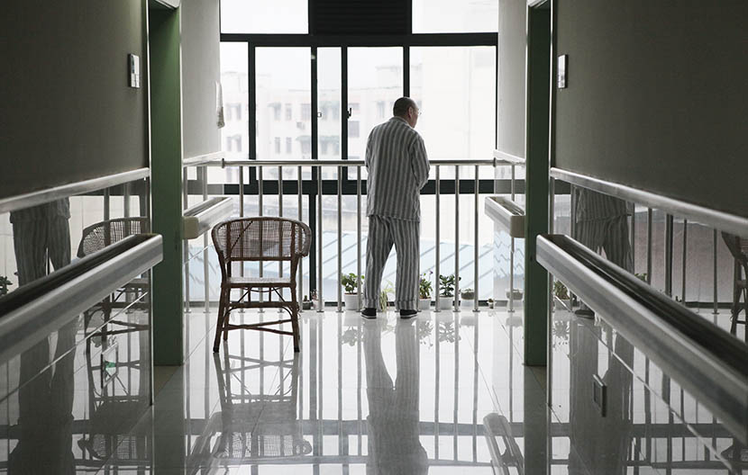 A man stands by a window at the end of the hallway at Putuo District Shiquan Street Community Health Service Center, Shanghai, May 5, 2013. Gao Zheng/Sixth Tone